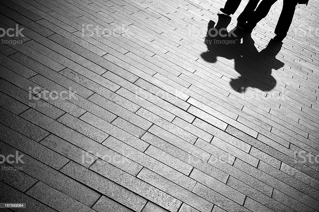 Shadow Businessmen Walk on Gray Paving Stones royalty-free stock photo