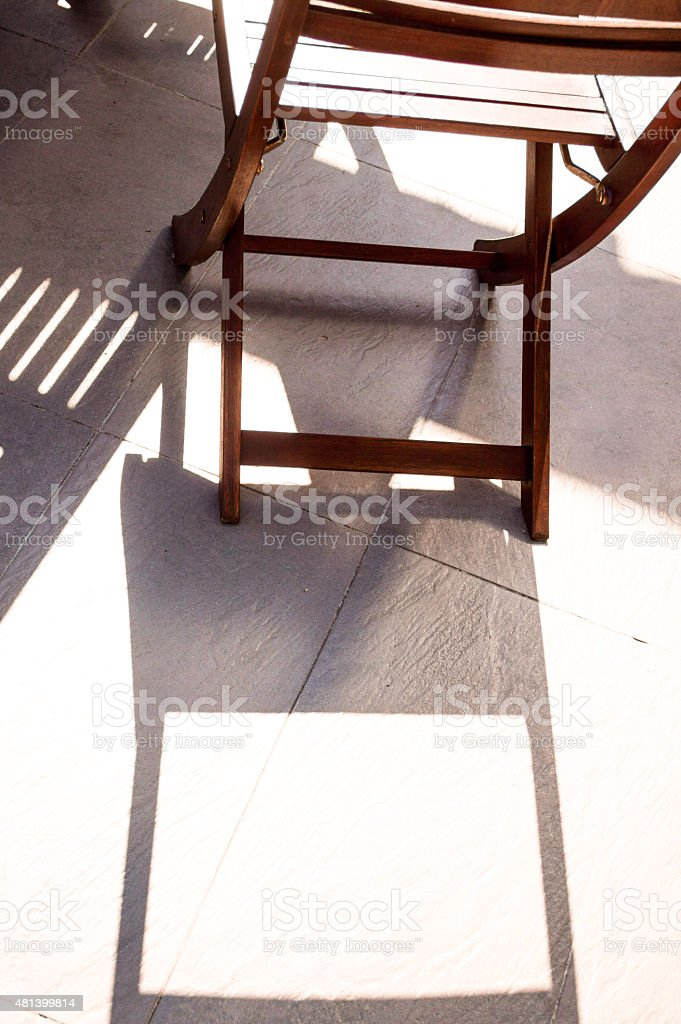 Shadow of a Deck Chair on a Balcony in Sun royalty-free stock photo