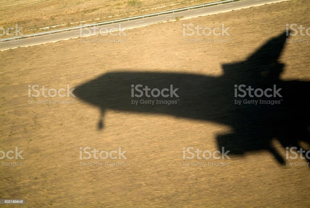 Shadow of a flying airplane taking off stock photo