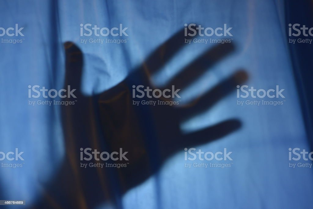 A shadow of a hand on a dark shower curtain stock photo
