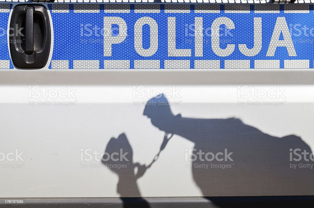Shadow of a man in handcuffs on police car. royalty-free stock photo