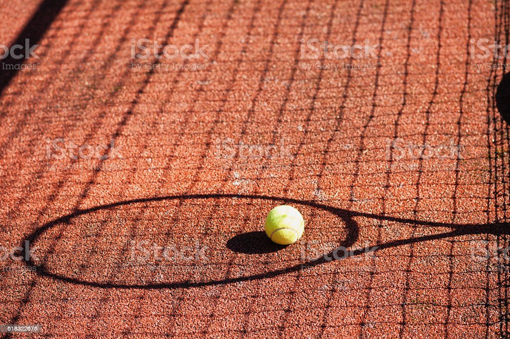 Shadow of a tennis racket and ball on court stock photo