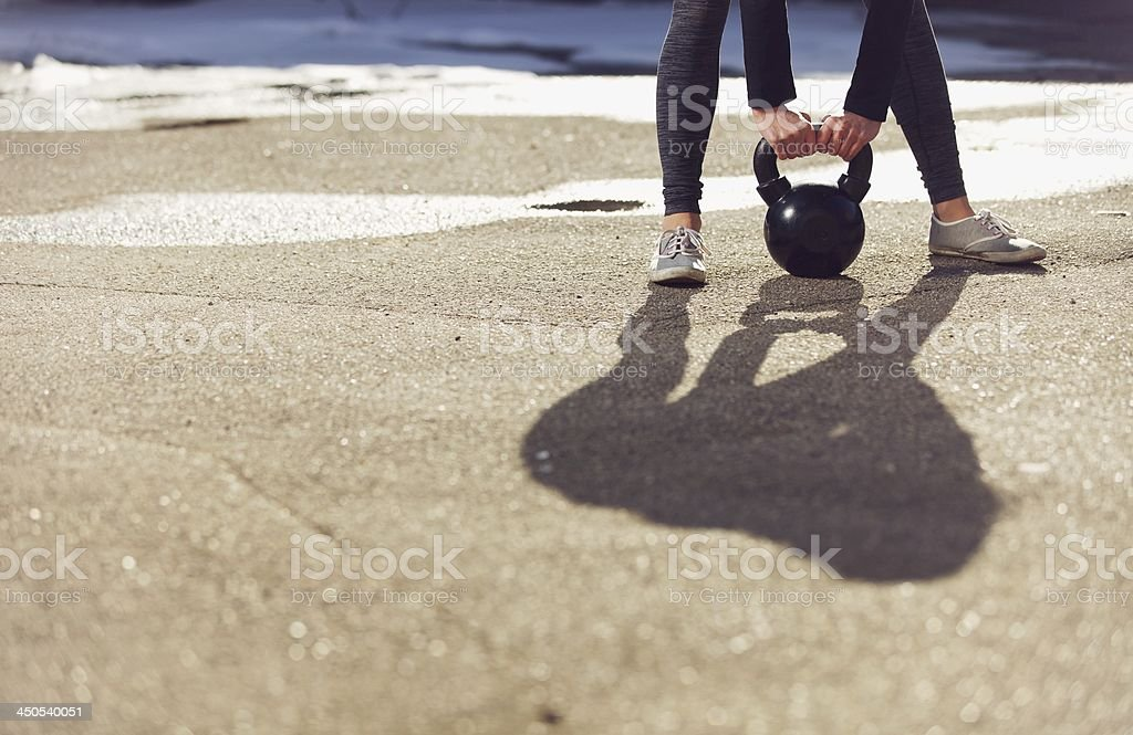 Shadow of a trainer lifting kettlebell stock photo