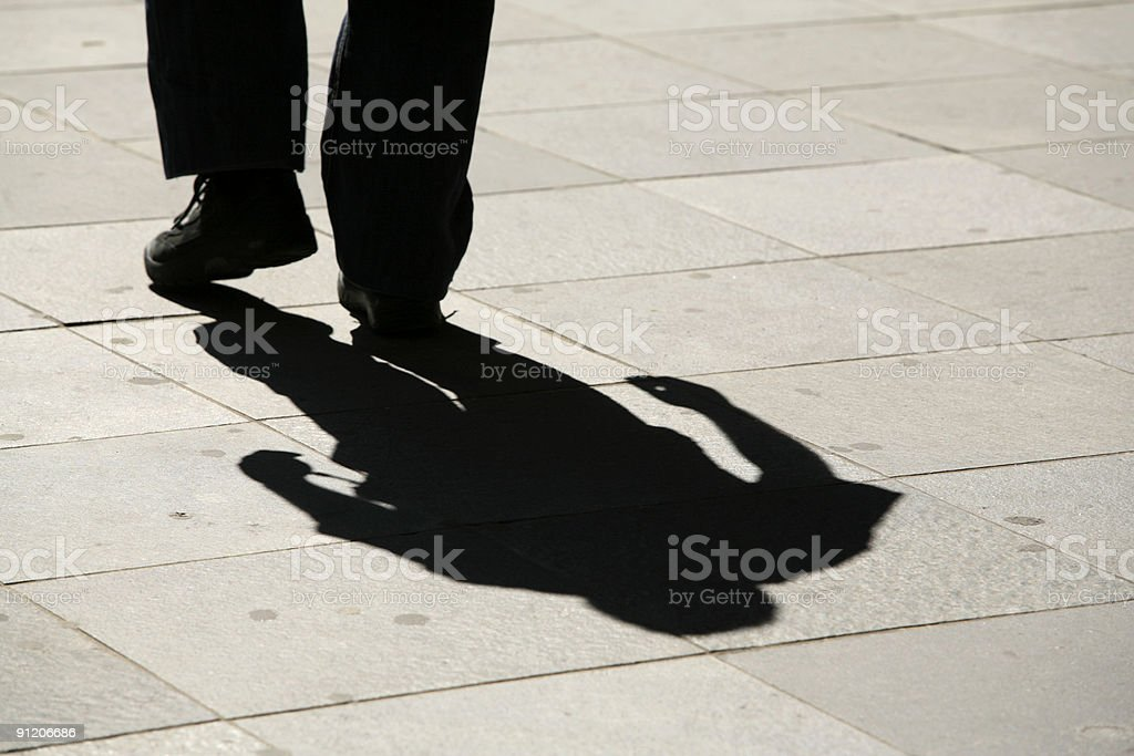 shadow of a walking man on his way to ... royalty-free stock photo