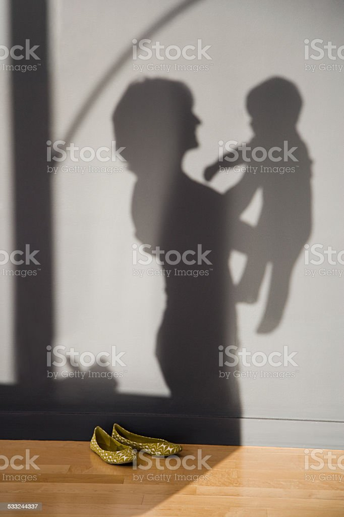 shadow of a woman holding a baby stock photo