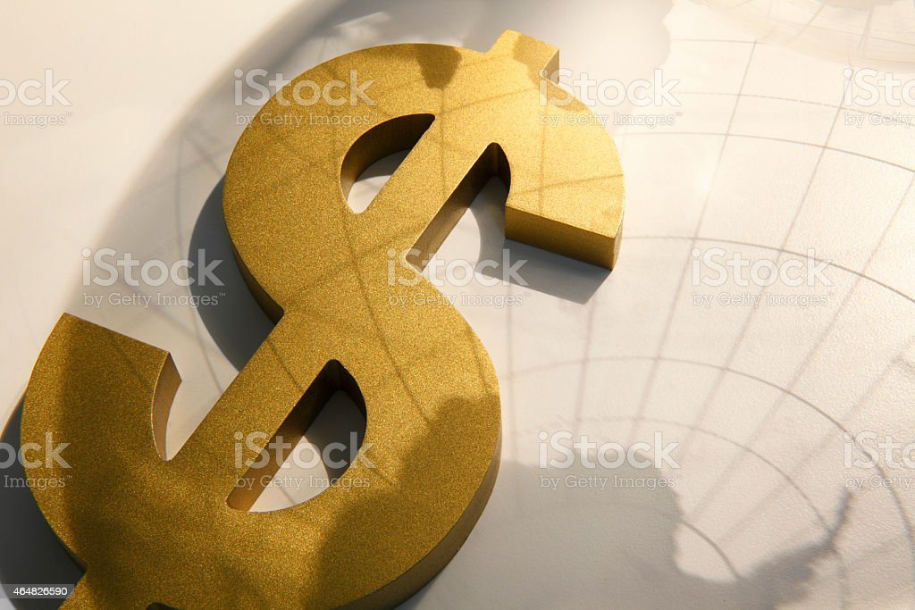 Shadow of globe cast over dollar symbol stock photo