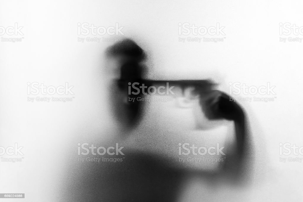 Shadow of horror man killer with a gun in his hand.Put a gun to his own head.Dangerous man behind the frosted glass.Mystery man.Black and white picture.Blur picture. stock photo