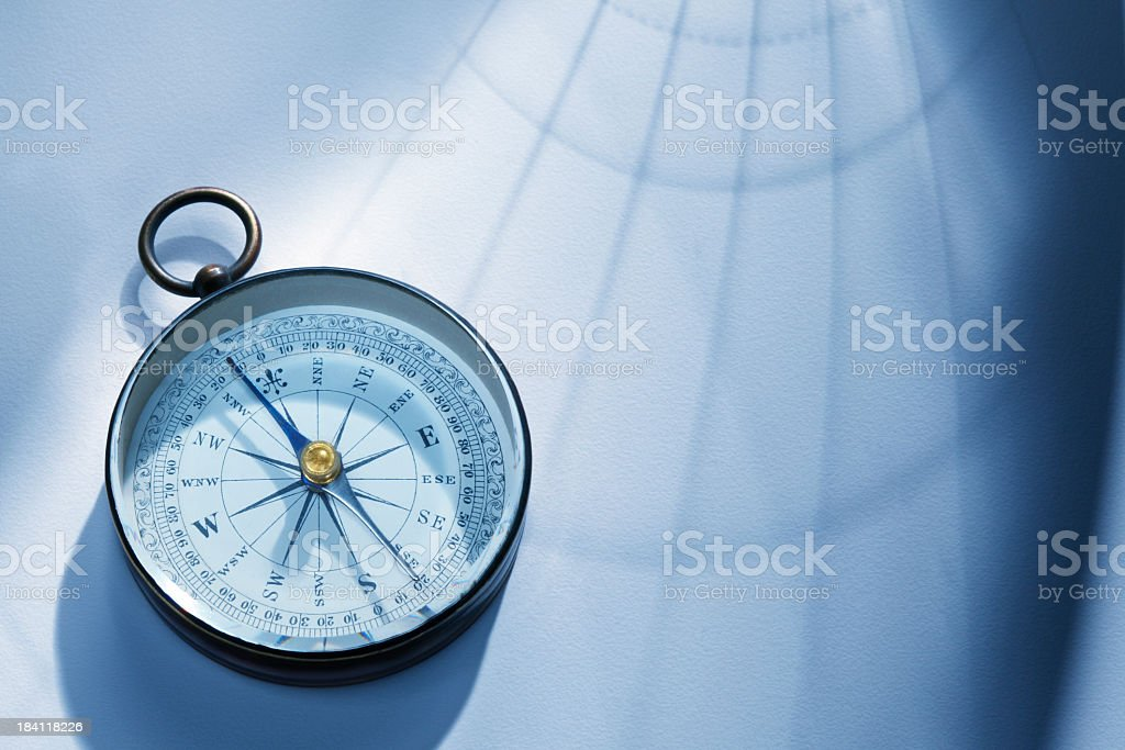 Shadow Of Latitude And Longitude Lines Cast Onto A Compass stock photo