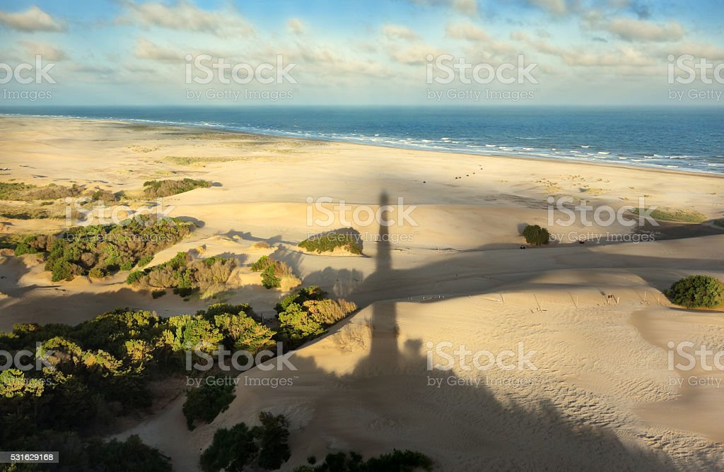 Shadow of lighthouse in South Atlantic beach stock photo