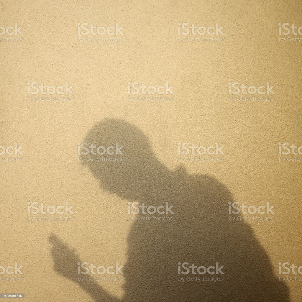 Shadow of man holding a phone stock photo