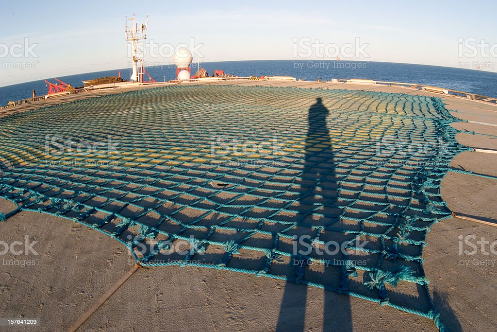 shadow of man on oil rig helideck royalty-free stock photo
