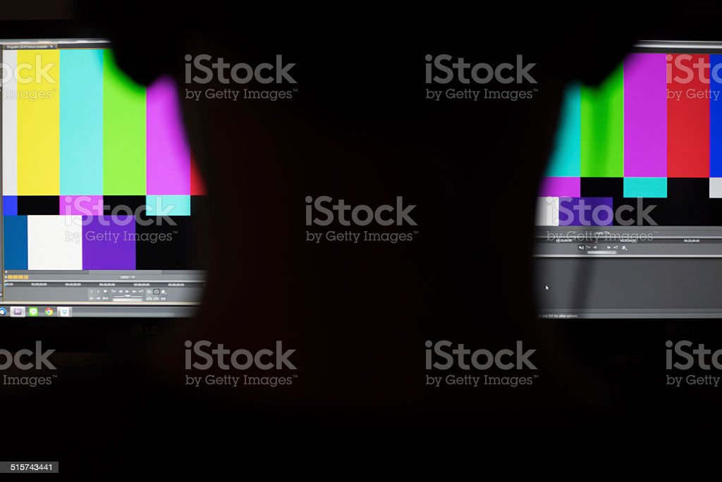 shadow of man working in front of colorbars monitor workstation stock photo