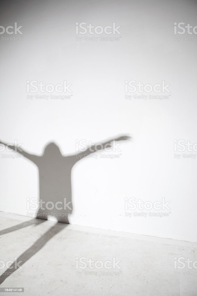 Shadow of person with arms out royalty-free stock photo