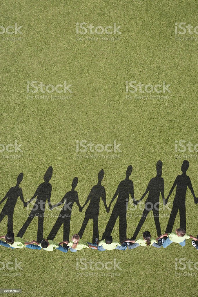 Shadow on grass of children holding hands royalty-free stock photo