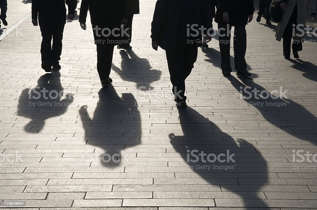 Shadow Team of Commuters Walking on Smooth Stone Walkway royalty-free stock photo