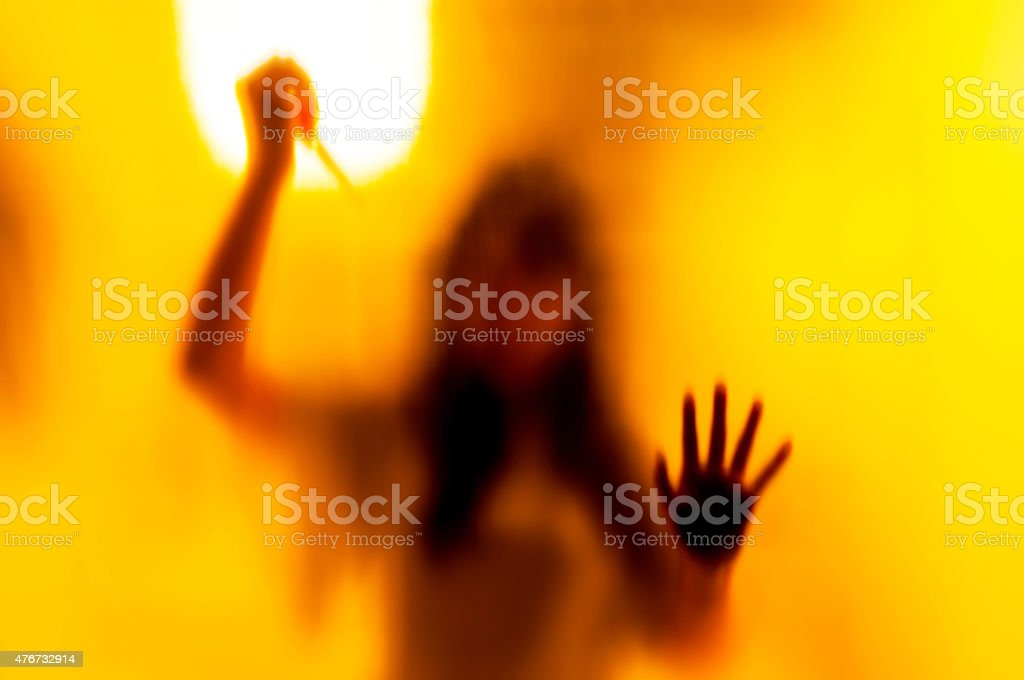 Shadow woman figure with a  scissors behind glass stock photo