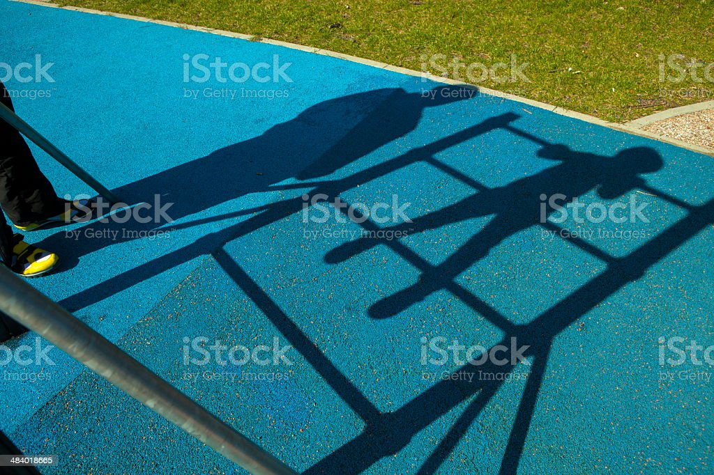 Shadows  adult on playground royalty-free stock photo