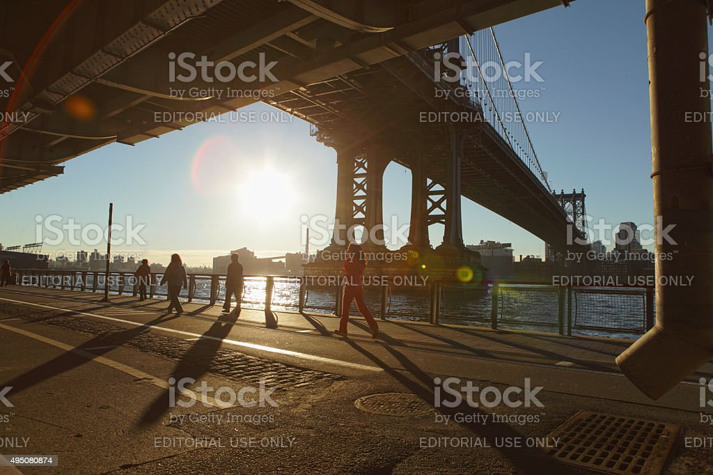 Shadows and people at sunrise under the Manhattan Bridge NYC stock photo