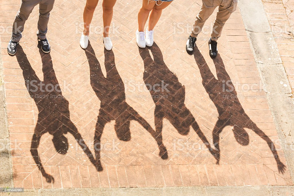 Shadows of friends holding and raising hands  together stock photo
