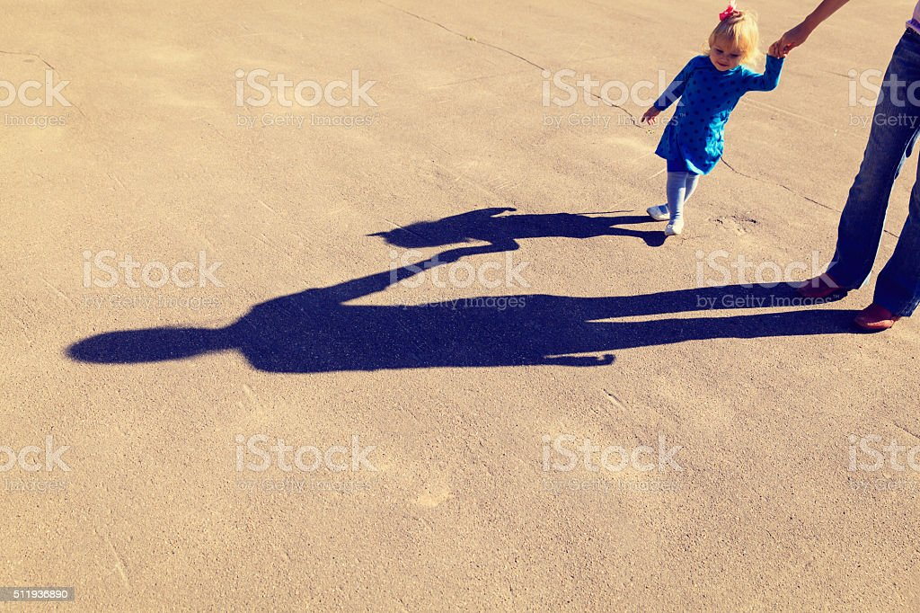 Shadows of mother and daughter holding hands on the road stock photo