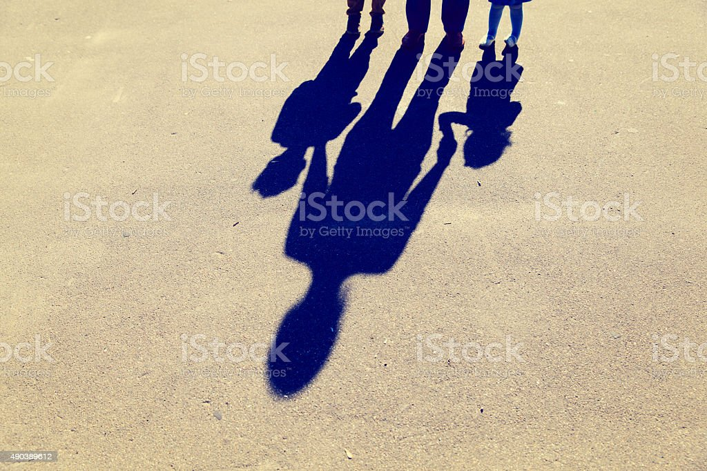 Shadows of mother with son and daughter holding hands stock photo