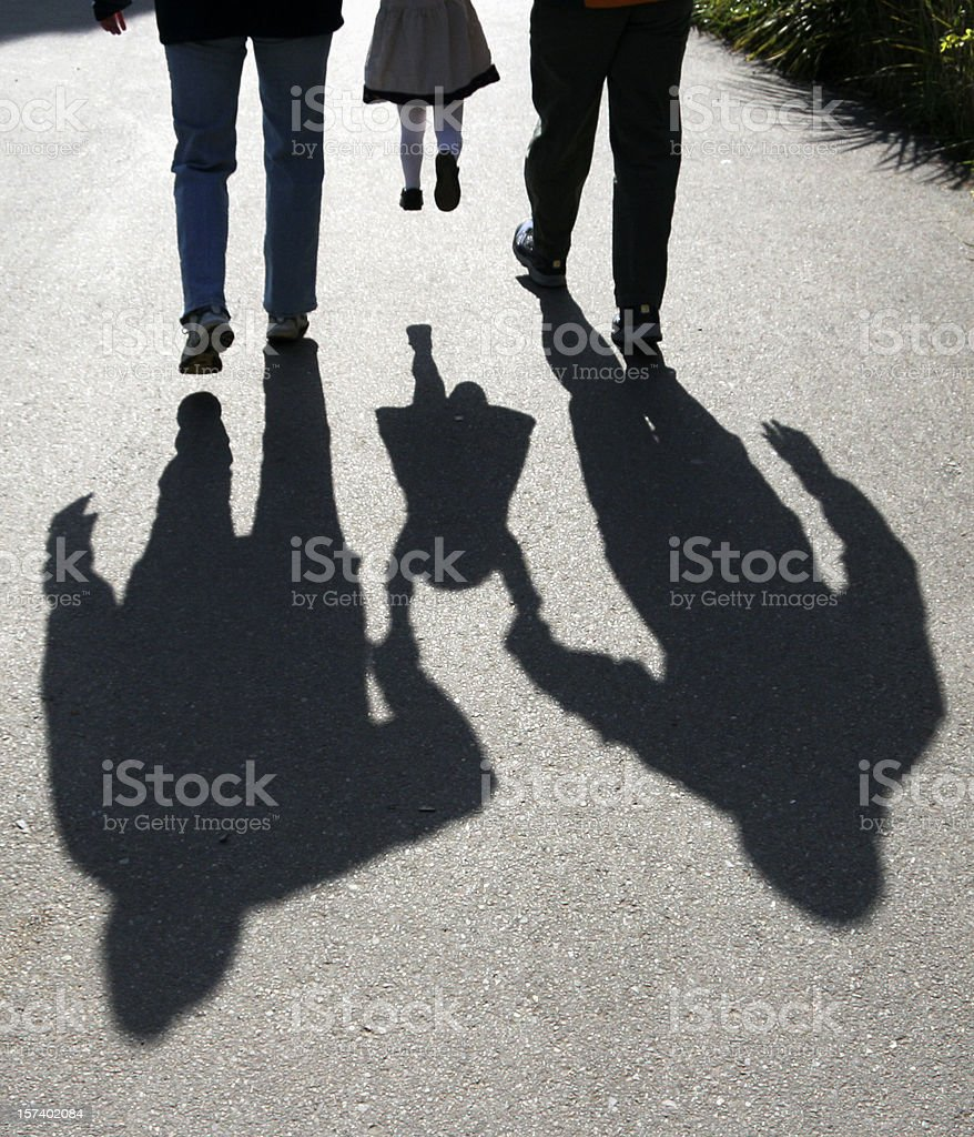 shadows of parents lifting child royalty-free stock photo