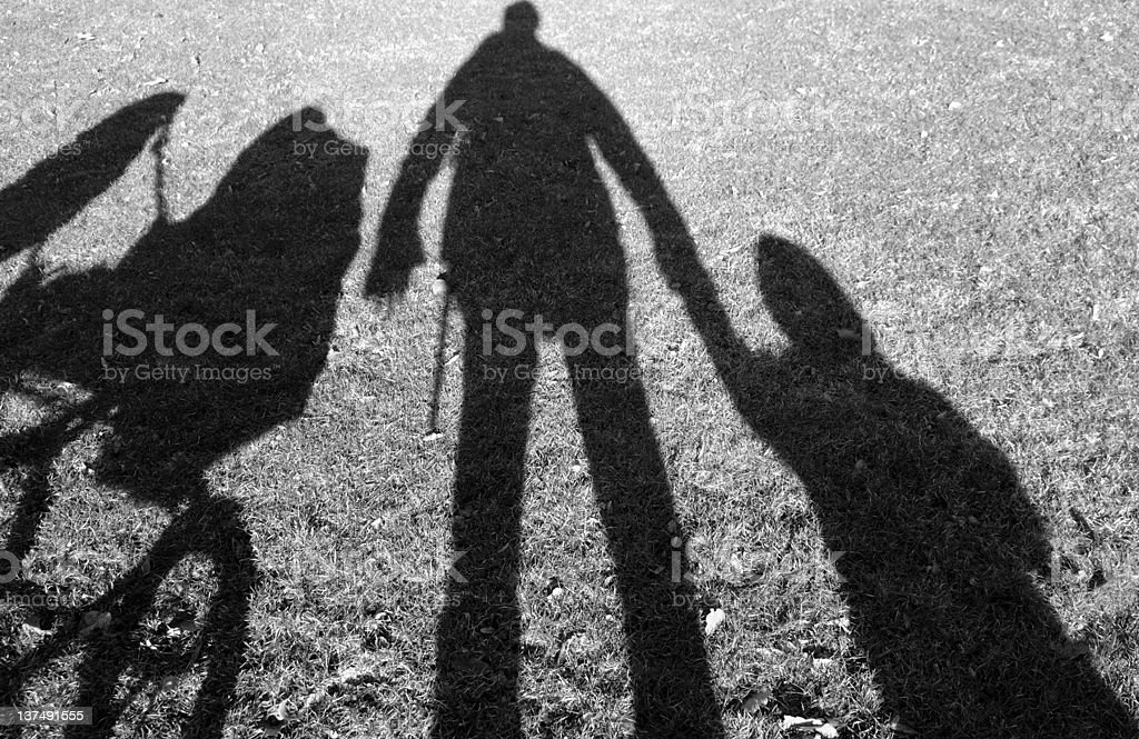 Shadows of person holding hands with a baby and a stroller stock photo