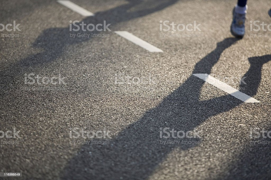 shadows of running athletes on an asphalt road royalty-free stock photo