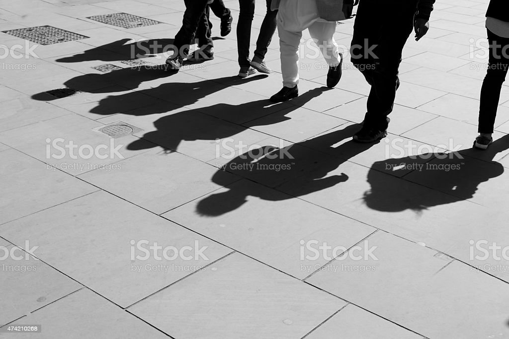 Shadows of six walking pedestrians projected on the sidewalk. stock photo