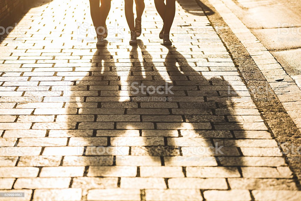 Shadows of three girls walking in the city stock photo