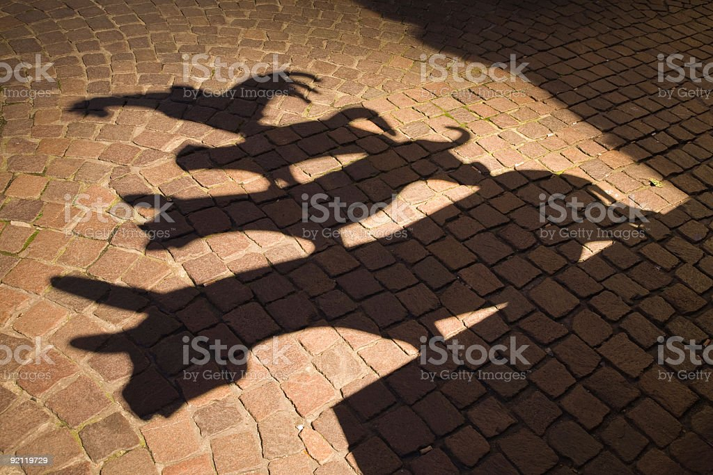 Shadows of town musicians against a cobblestoned path stock photo
