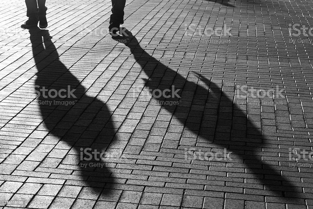 Shadows Of Two People Walking On The Street stock photo