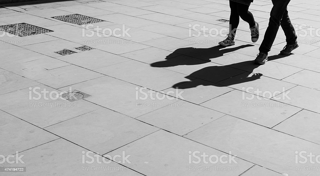 Shadows of two walking pedestrians projected on the sidewalk. stock photo