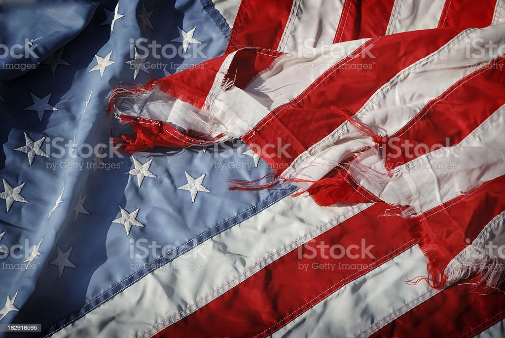 Shadows on a Faded Worn Stars and Stripes American Flag stock photo
