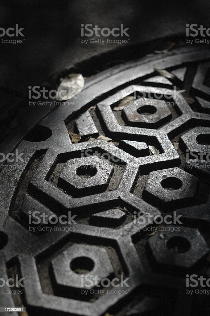 Shadows on a manhole cover stock photo