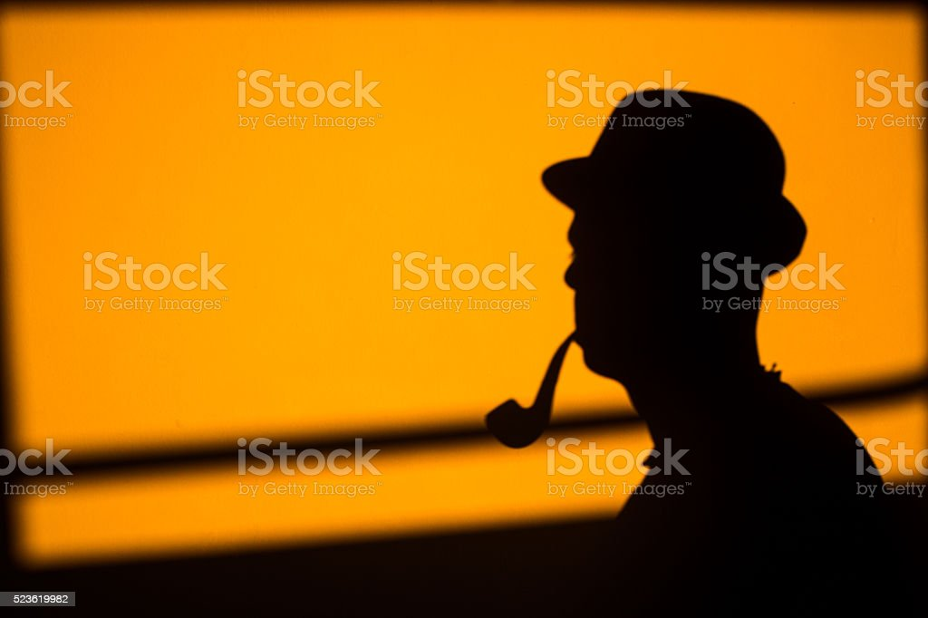 Shadows on the wall, the man with hat and pipe stock photo