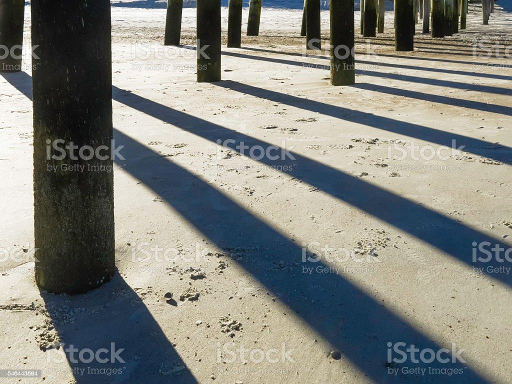 Shadows underneath beach pier stock photo