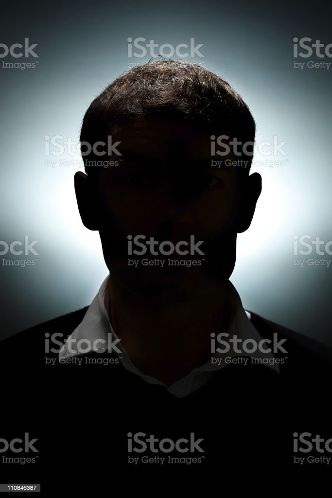 A shadowy silhouette of a man in a sweater vest stock photo