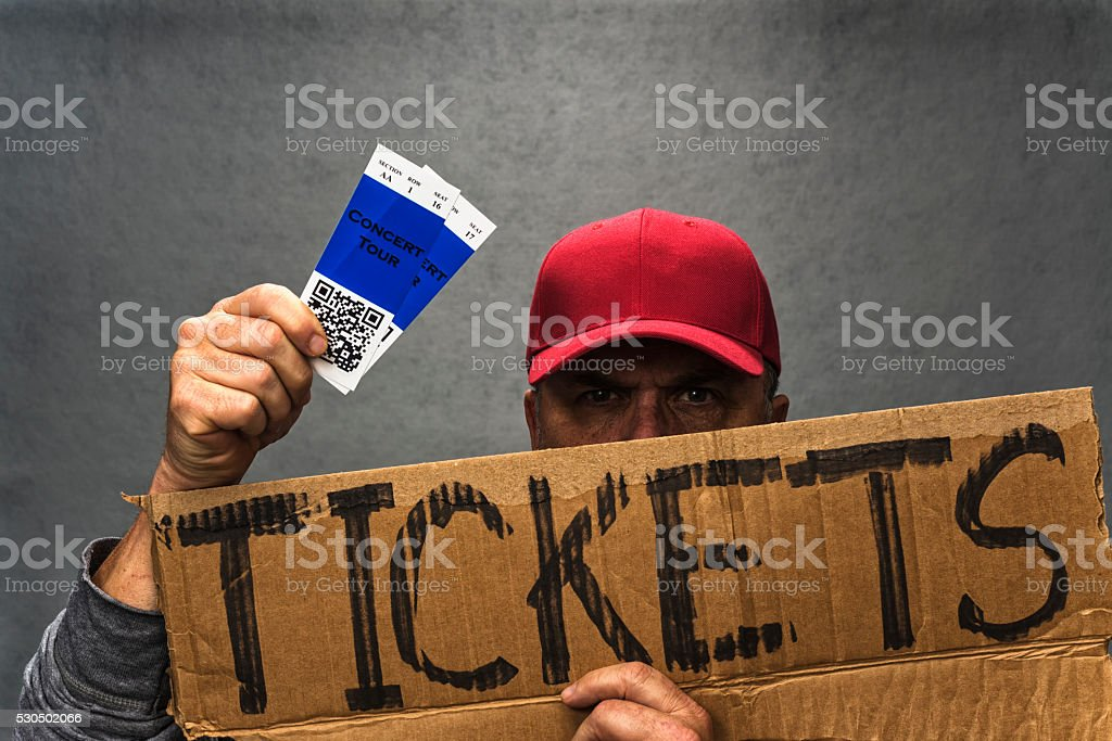 Shady character scalping a pair of concert tickets stock photo