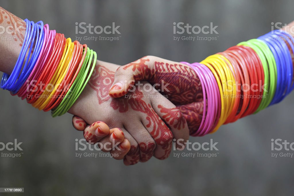 Shaking hands decorated with colorful bracelets stock photo
