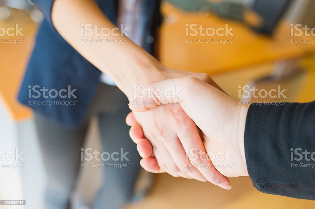Shaking hands in office stock photo