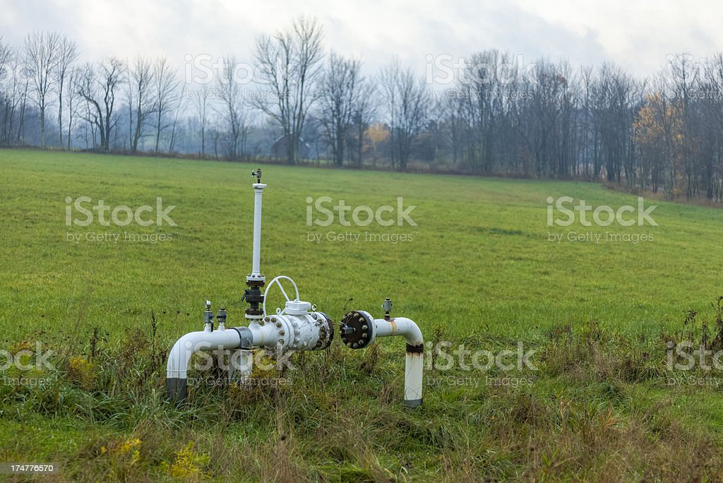 Shale gas pipelines in a green field with a gray sky stock photo