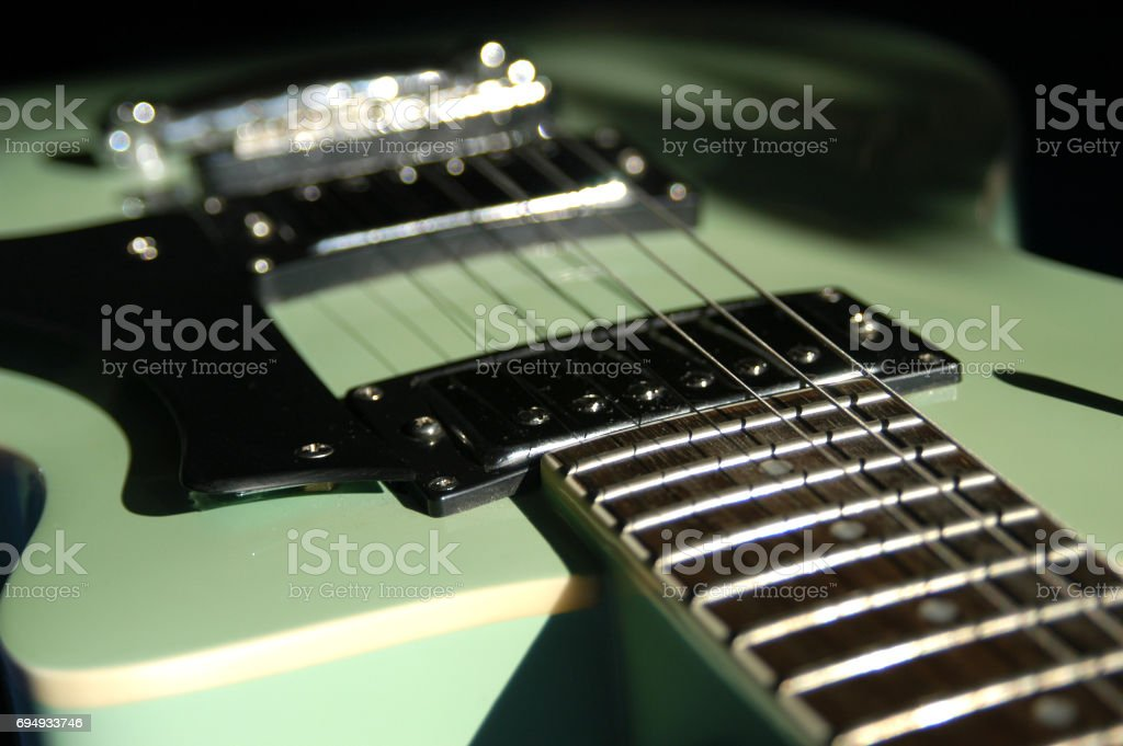 Shallow depth of field macro lens shot of vintage electric guitar lit...