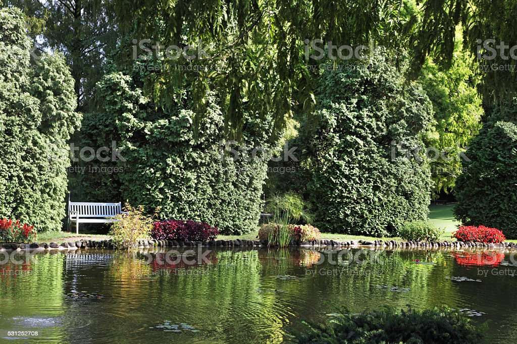Shallow pond and elegantly trimmed trees stock photo