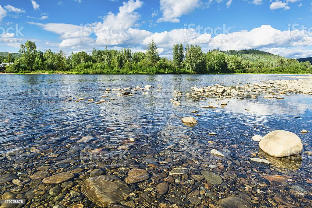 Shallow water of the Klondike River filled with rocks stock photo