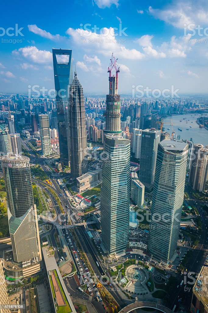 Shanghai Pudong skyscrapers soaring blue skies above crowded cityscape China stock photo