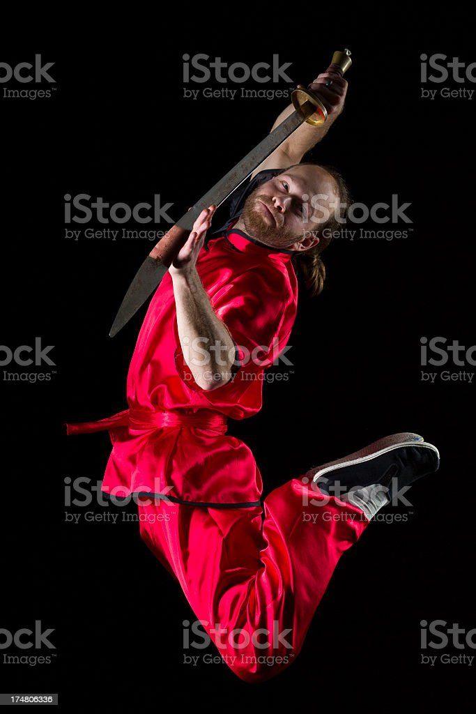 Shaolin Kung Fu fighting position with Dao sword in midair stock photo