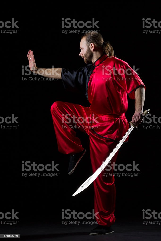 Shaolin Kung Fu fighting position with Dao sword on black stock photo