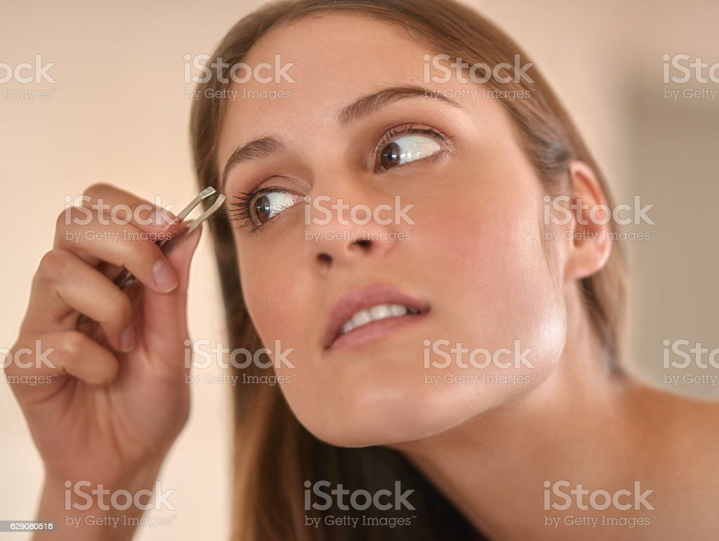 Shaping her brows to perfection stock photo