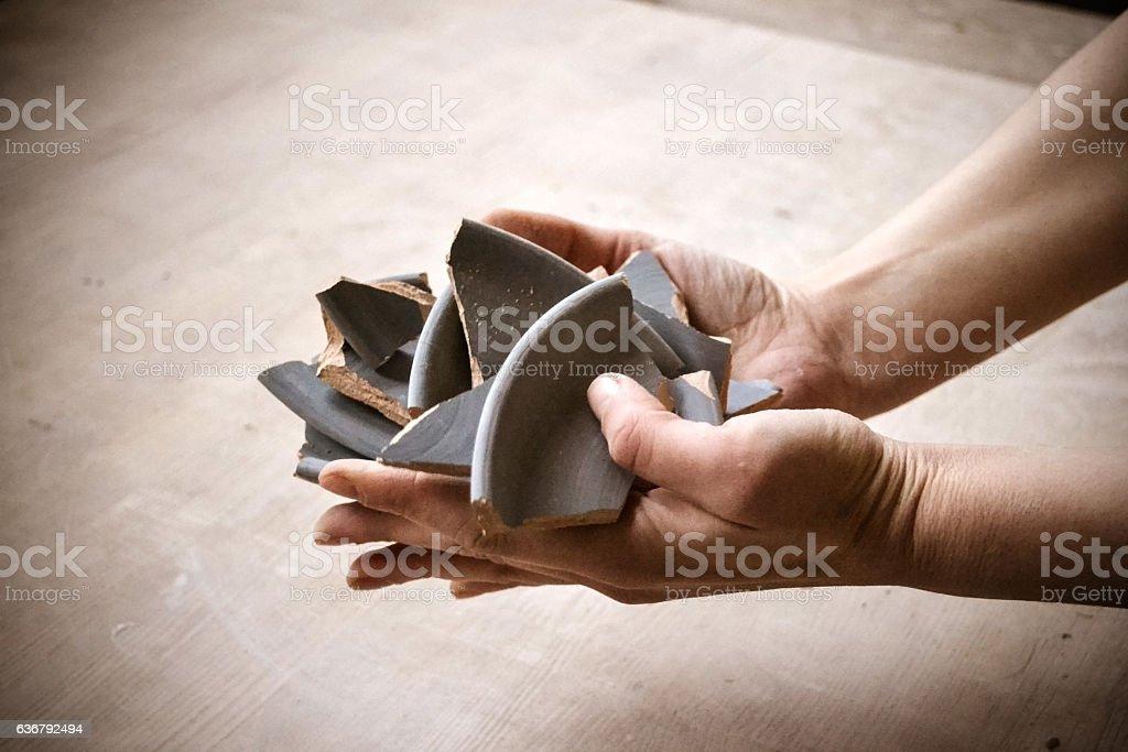 Shards of broken plate in hands stock photo